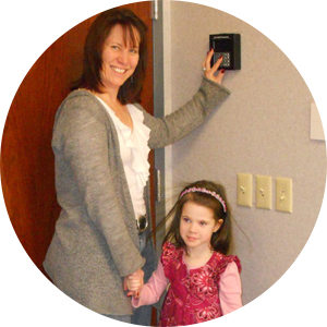 Picture of parent using time clock biometric childcare check-in system connected to door security.